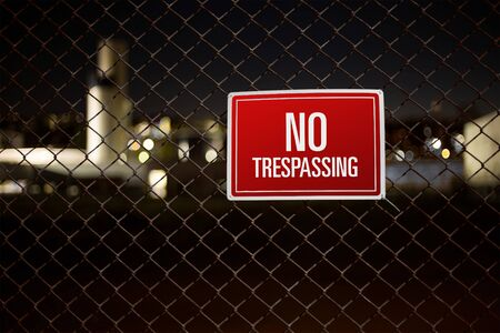 trespassing: Private property no trespassing sign warning on a chainlink fence Stock Photo
