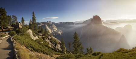 Panorama with Half Dome and Yosemite Valley and morning mist on walleys and hills during sunny morning in Yosemite National Park