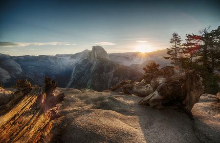 puesta de sol: Half Dome y el valle de Yosemite en el Parque Nacional Yosemite en colorido atardecer y troncos de �rboles viejos Foto de archivo