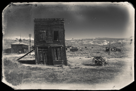 crooked: Very old sepia vintage photo with abandoned and crooked western city building built during gold rush, Bodie Stock Photo
