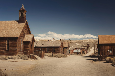 to rush: Colored vintage old looking photo of empty streets of abandoned ghost town Bodie in California, USA in the middle of a day.
