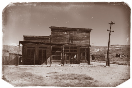 western usa: Very old sepia vintage photo with crooked abandoned building in old western city in Bodie Ghost Town
