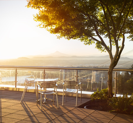 mount hood: Table with three chairs on a beautiful view with mount Hood and tree with branches and leaves during early sunrise with sunglow. Stock Photo