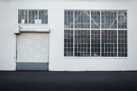 rolling garage door: Detail of warehouse building with white walls, rolling door and large window taken straight from the front Stock Photo