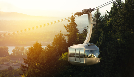 Detail of aerial tram in Portland, Oregon transporting people to and from the hilltop, with landscape and sunlight glow in the background