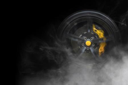 Geïsoleerde generieke sport auto wiel met gele breaks drijven en roken op een zwarte achtergrond Stockfoto