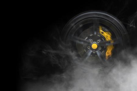 Isolated generic sport car wheel with yellow breaks drifting and smoking on a black background