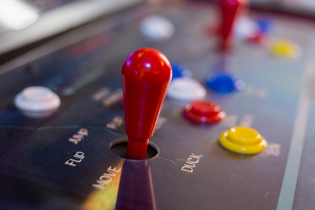 arcade: Detail of a red joystick and buttons on an old arcade game in a gaming room