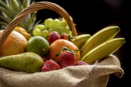 garden key: Basket full of fruit (banana, strawberry, pineapple, orange, pear, apple on a dark background ? low key Stock Photo