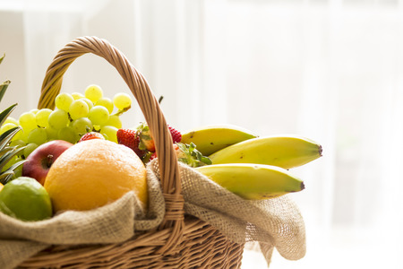 high key: Horizontal Closeup on basket full of fruits from side on light background - high key Stock Photo