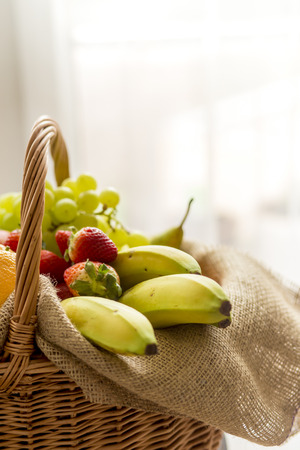 high key: Vertical Closeup on basket full of fruits on a light background - high key Stock Photo