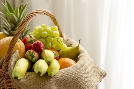 high key: Basket full of fruits on a light background - high key