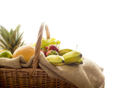 high key: Horizontal closeup detail of a basket full of fruit (banana, strawberry, pineapple, orange, pear, apple) on light background - high key