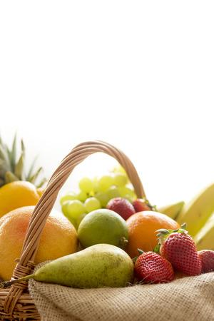 fruit basket: Vertical closeup detail of a basket full of fruit (banana, strawberry, pineapple, orange, pear, apple) on light background - high key Stock Photo