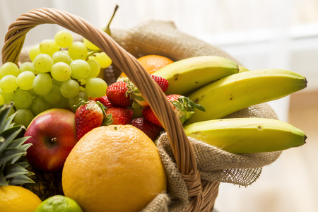 Horizontal closeup detail of a basket full of fruit (banana, strawberry, pineapple, orange, pear, apple) on light background - high key