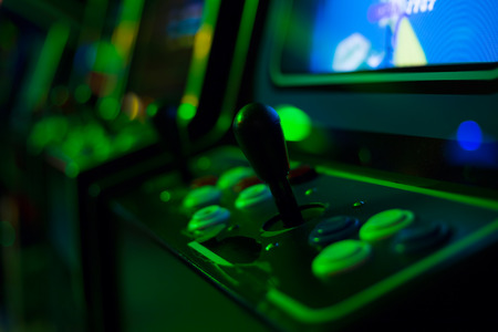 Detail of a black joystick and buttons on an old arcade game in a gaming room with green lights