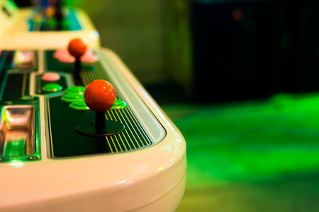 Detail of a red rounded joystick and buttons on an old arcade game in a gaming room Stock Photo