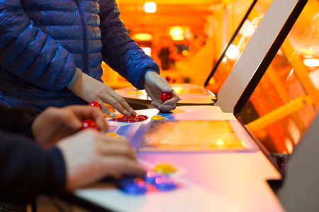 Detail of players hands interacting and playing with joysticks and buttons on an old arcade game in a gaming room