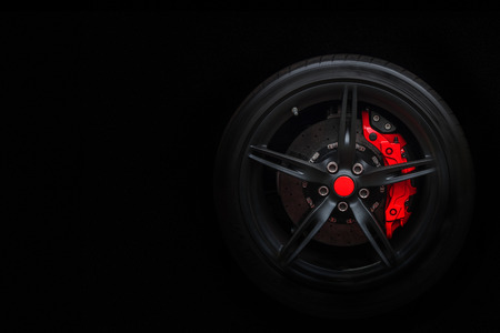 Isolated generic sport car wheel with red breaks and dark rim on a black background