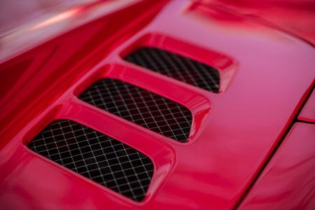 engine bonnet: Detail of red super-sport car vents on a bonnet