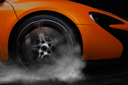 side keys: Orange super sport car from side with detail on spinning wheel, smoking and doing burnouts on a dark background