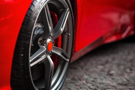 휠 타이어에 초점을 맞춘 빨간색 슈퍼 스포츠 자동차 전면 측면의 세부 사항