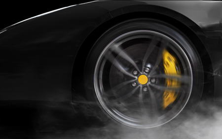 car front: Isolated generic black sport car with detail on wheel with yellow breaks drifting and smoking on a black background Stock Photo