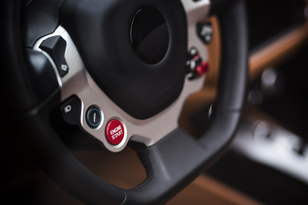 Super Sport Car Interior Detail on Red Engine Start Button on a Wheel