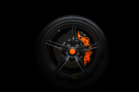 breaks: Isolated generic sport car wheel with orange breaks a black background Stock Photo