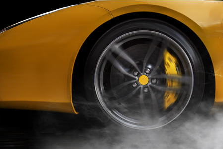 Isolated generic yellow sport car with detail on wheel with yellow breaks drifting and smoking on a black background