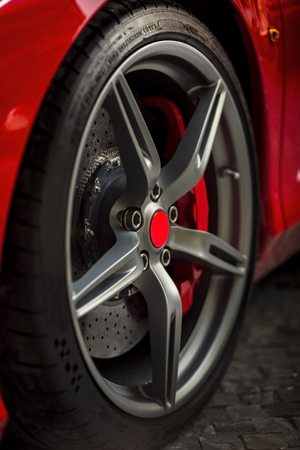 breaks: Detail on red super sport car wheel with red center and red breaks and metal rims