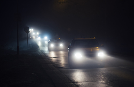 Line of cars with shining headlights in a night fog during winter