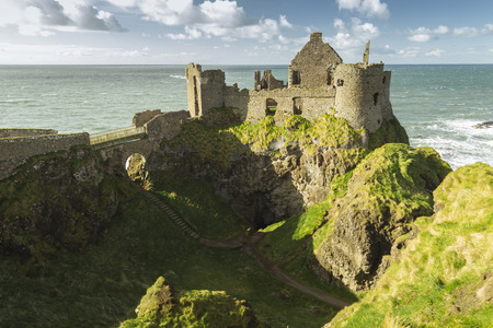 Dunluce Castle, Antrim, Northern Ireland during sunny day with semi cloudy sky Editorial