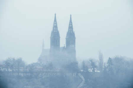 Old Vysehrad Basilica of saint Peter and Pavel covered in fog during foggy day