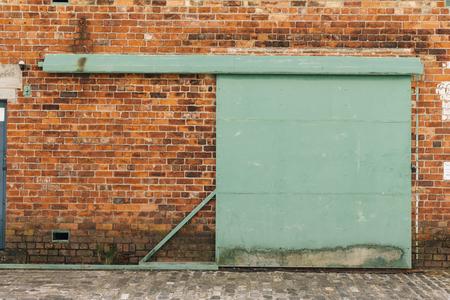 Dark Brick Wall with Metal Gate Door