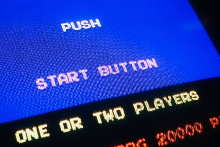 Detail Macro of an old vintage video game with text Push start button, with option to select one or two players