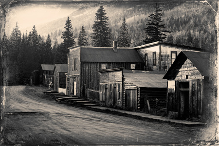 Vintage photo of old western buildings in the middle of mountains