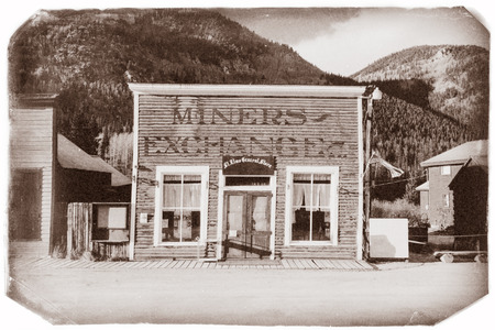 Vintage Photo of an old General store with miners exchange in old western town in the middle of mountains
