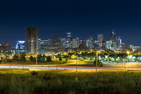 Long Exposure of Denver City Skyline during night with green grass and light trails Stock Photo