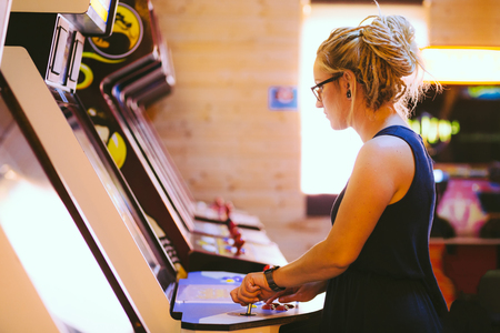 Young female with blonde dreadlock hair and a blue dress is playing an old arcade video game in a gaming bar filled with sun Stock Photo
