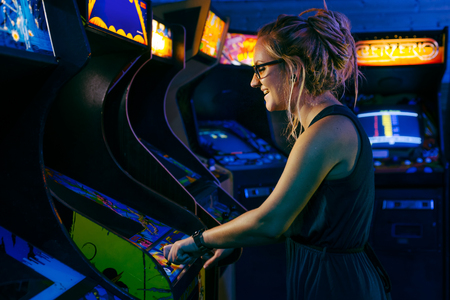Smiling young female with blonde dreadlock hair and a blue dress is playing an old arcade video game in a dark gaming bar with various games in the background