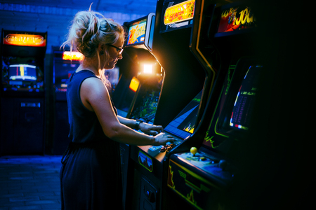 Attractive young female with blonde dreadlock hair and a blue dress is playing an old arcade video game in a dark gaming bar with various games in the background