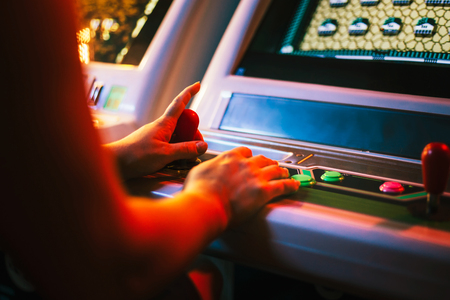 A Player holding a joystick and playing an arcade video game in a gaming bar area Banque d'images