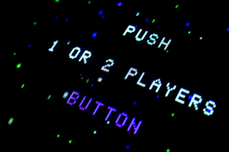 Detail on an old arcade video screen with text Push 1 or 2 players button with color splashes background Stock Photo