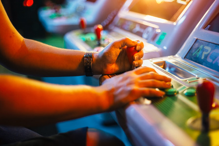 Players hands holding a joystick and buttons while playing on a white arcade video game in gaming bar Stock Photo