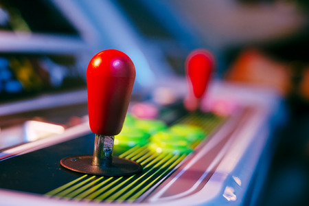 Red Joystick of an Old Arcade Video Game with Blurred Background Stock Photo