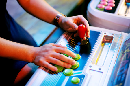 Players hands holding red Joystick of an Old Arcade Video Game with Blurred Background Stock Photo