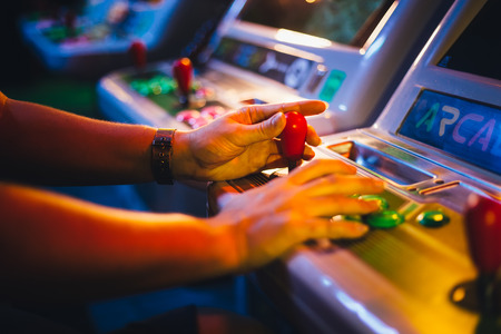 Detail on Hands with Arcade Joystick Playing Old Arcade Video Game