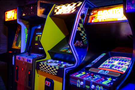 Row of Old Arcade Video Games with Shining Displays in a Dark Gaming Room Stock Photo