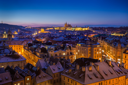 Prague Castle with snowy rooftops during late christmas sunset with blue sky and glowing street lights